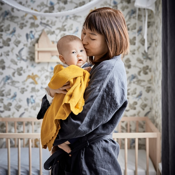 A mother stands in front of a cot in a bedroom and holds her baby who is wrapped inside a dark yellow SOLGUL blanket.