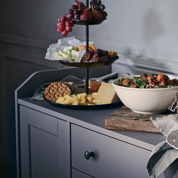 灰色的HAUGA 豪嘉 餐边柜,上面放着一碗食物和一个三层的INBRINGANDE 因布林刚德 上菜架,上面放着奶酪、饼干和水果。