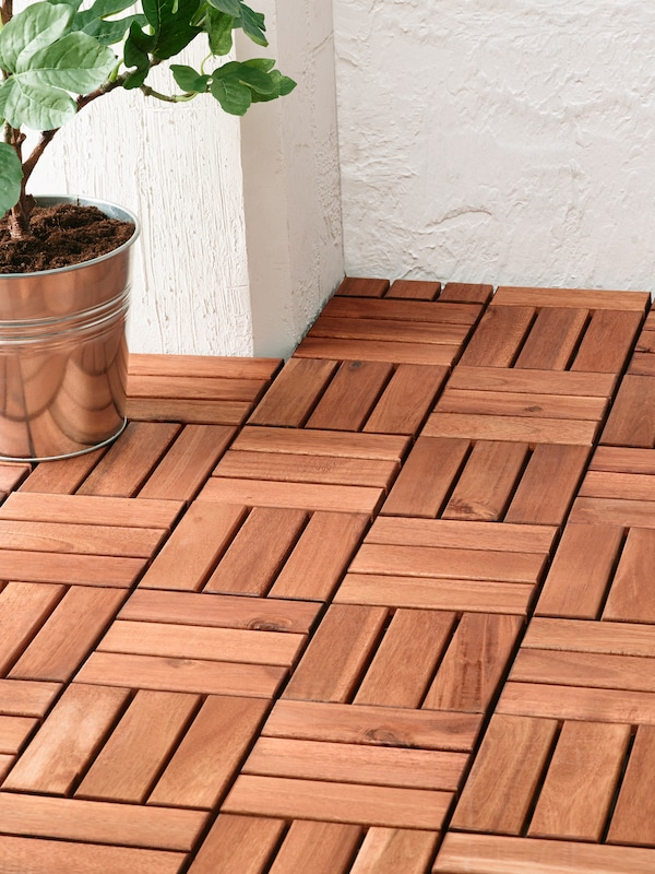 Wooden flooring that fits the outdoor space perfectly, with a potted plant in a metal plant pot and a white wall behind.