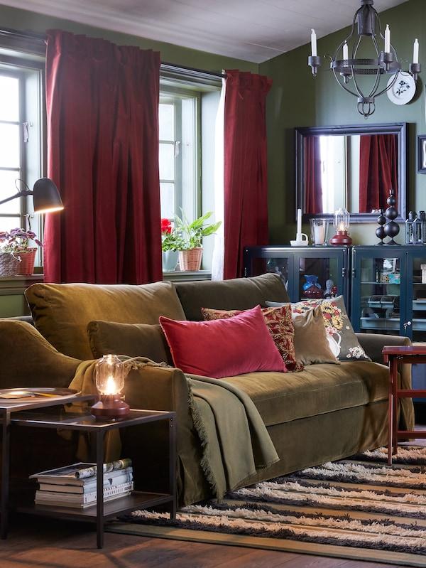 客厅里的两个窗户配有红褐色的SANELA 桑尼拉 窗帘;前面是一张绿色沙发,上面放着靠垫和一张ODDRUN 乌德鲁恩 休闲毯。