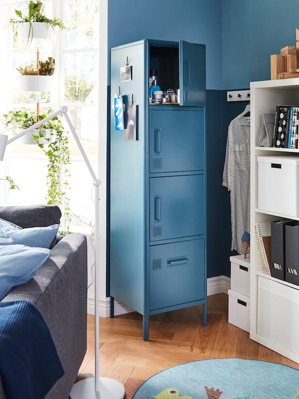一个蓝色储物柜,顶部储物格的柜门打开着;旁边是摆放着各种物品的白色搁架,以及一张沙发的背面。