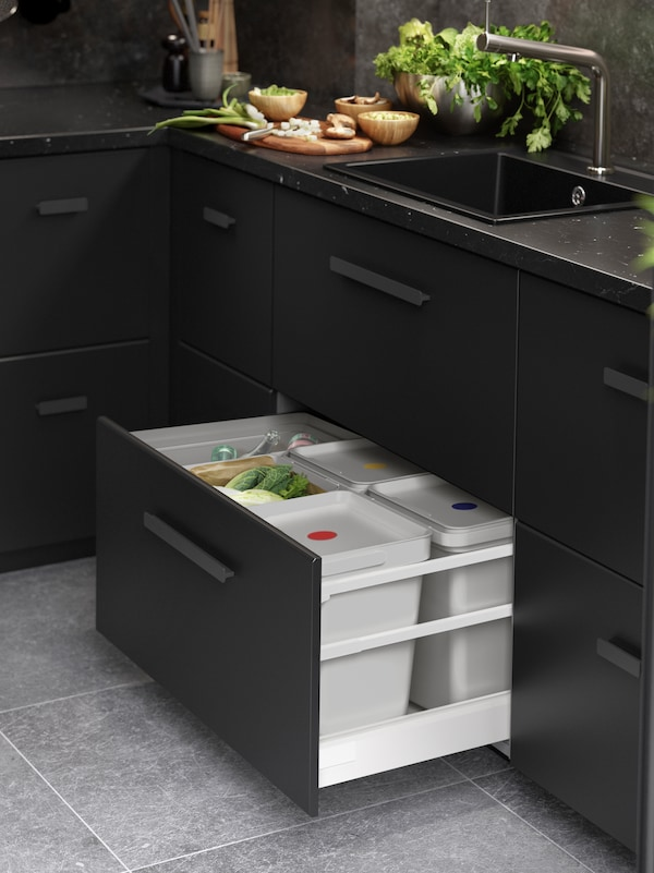 5 HÅLLBAR bins in an open drawer under a kitchen sink. 3 bins have lids with coloured dots on, the other two are open.