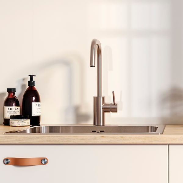 A white wall panel and a white kitchen front with leather handles under a sink. Bottles of soap are next to the sink.