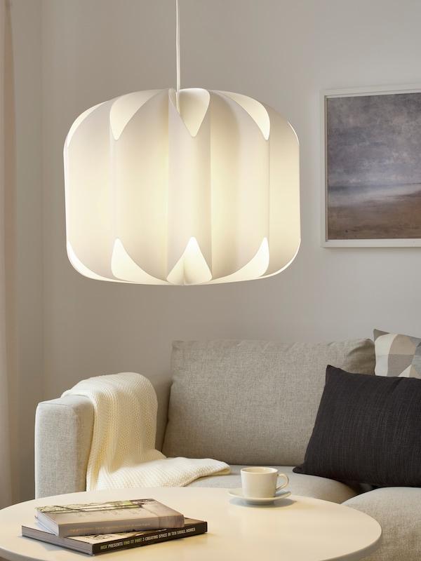 一盏白色吊灯下方是一张茶几,上面摆放着咖啡杯、茶碟和书,后边有一张带靠垫的灰色沙发。