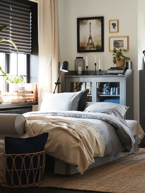 房间里有一张沙发床,后方是一个玻璃柜门,墙上挂着画,窗台上放着各式物品。