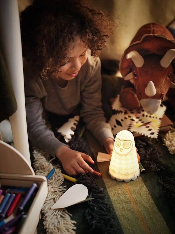 Under a table, a child plays with a SOLBO night light that illuminates his face and his toy dinosaurs.
