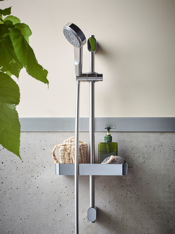 BROGRUND chrome-plated shower against a cream /creamy-grey speckled wall, with a soap dispenser and leaves of a green plant.