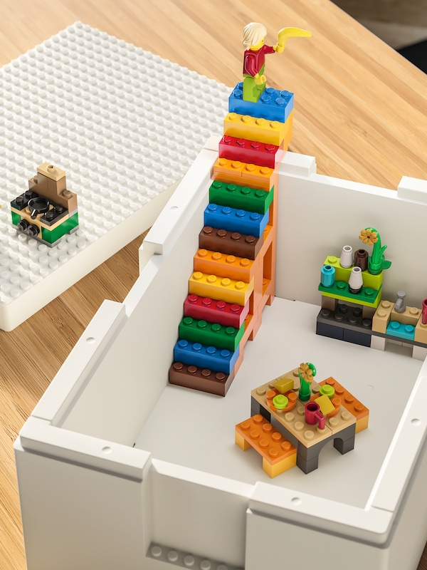 A white BYGGLEK box stands on a table with brightly-coloured LEGO constructions, including a set of stairs inside it.