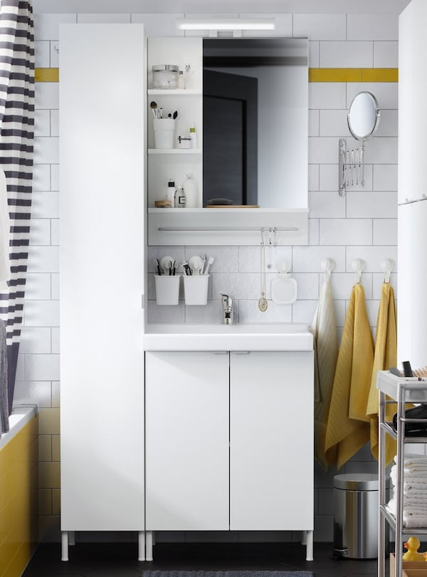 A yellow/white bathroom with a white wall cabinet with 1 door, a white wash-basin cabinet with 2 doors and a mirror cabinet.