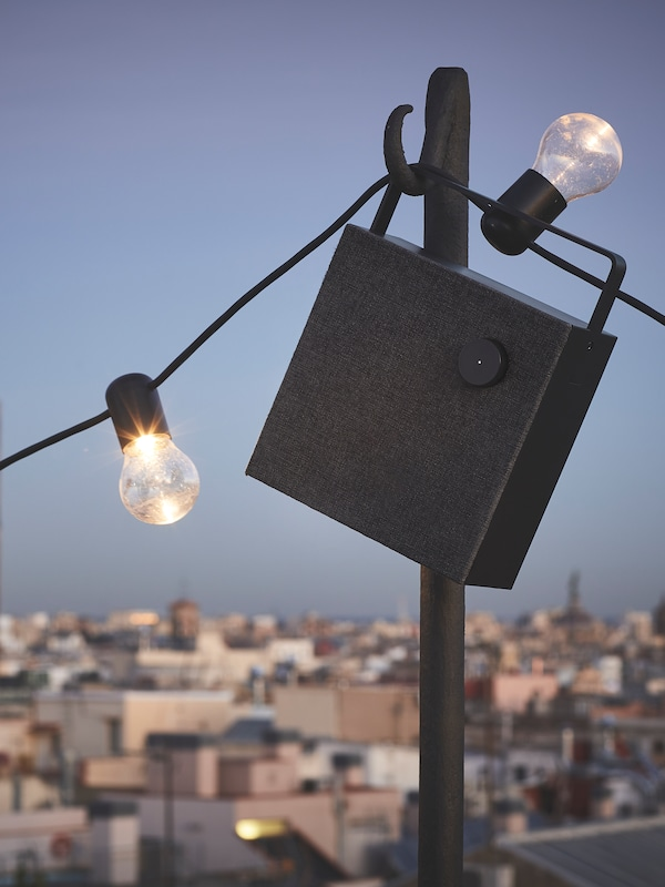 A black Bluetooth speaker hanging from a pole with strip lighting on a cable, a city rooftop scene in the background.