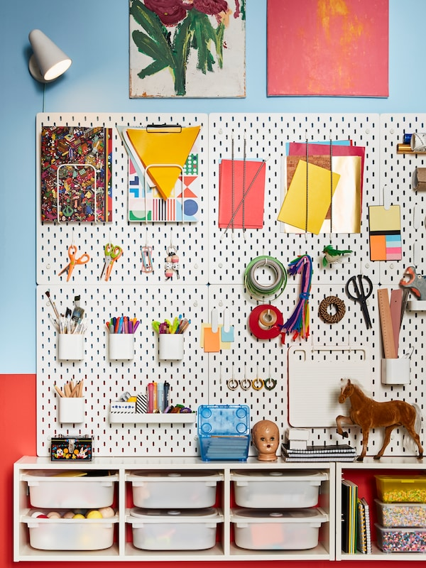 White SKÅDIS pegboards with accessories such as containers and hooks holding artist's supplies are attached to a wall.