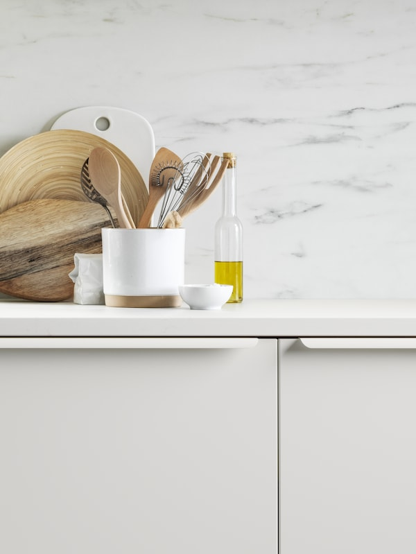 Two white kitchen cabinets below a white worktop and a wall panel with a white marble effect.