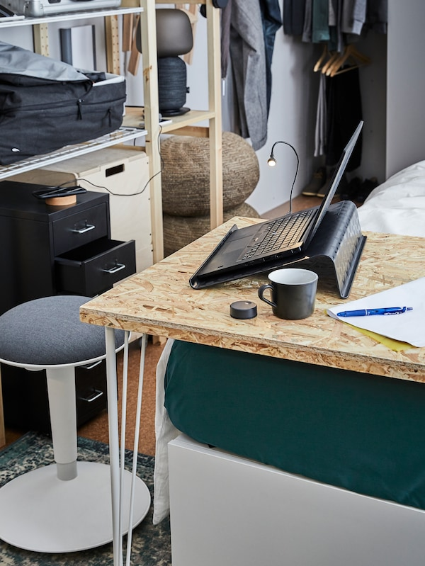 The corner of a table with an open laptop and a cup of coffee, a pen and paper, with a stool and storage behind.