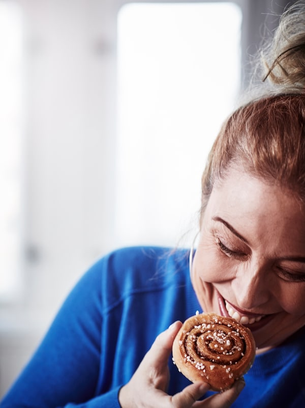 Close-up of a smiling, redhaired woman in a blue sweater as she holds a cinnamon bun up to her mouth.