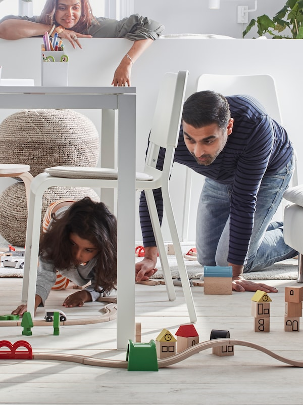 A father and child playing with a LILLABO train set that is running under and around a LANEBERG table and TEODORES chairs.