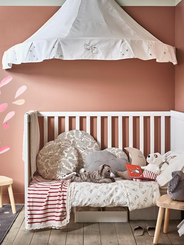 儿童房里放着SUNDVIK 桑维 婴儿床,上面摆了舒适的靠垫和毛绒玩具,天花板上是白色的RÖDHAKE 吕哈克 床篷。
