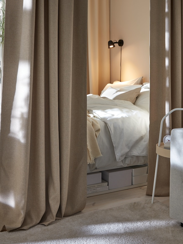 Part of a bed with BERGPALM bed textiles and a black lamp on the wall, seen between two, beige, ANNAKAJSA curtains.