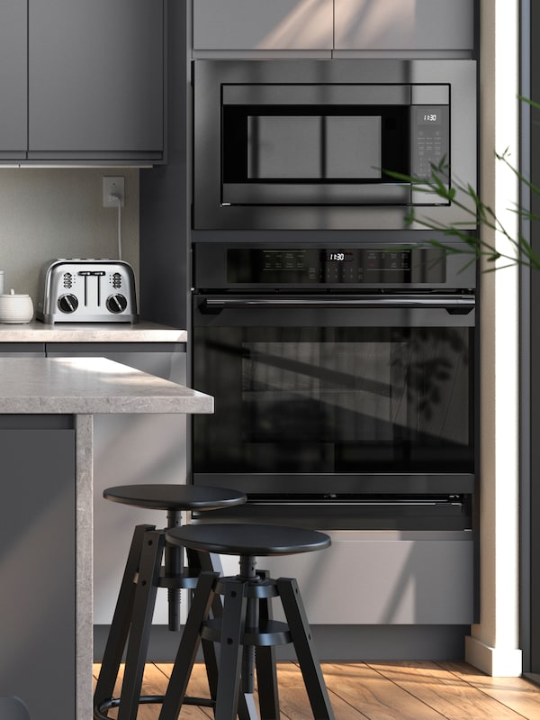 A kitchen in tones of grey with a built-in oven and microwave below two grey kitchen cabinets.