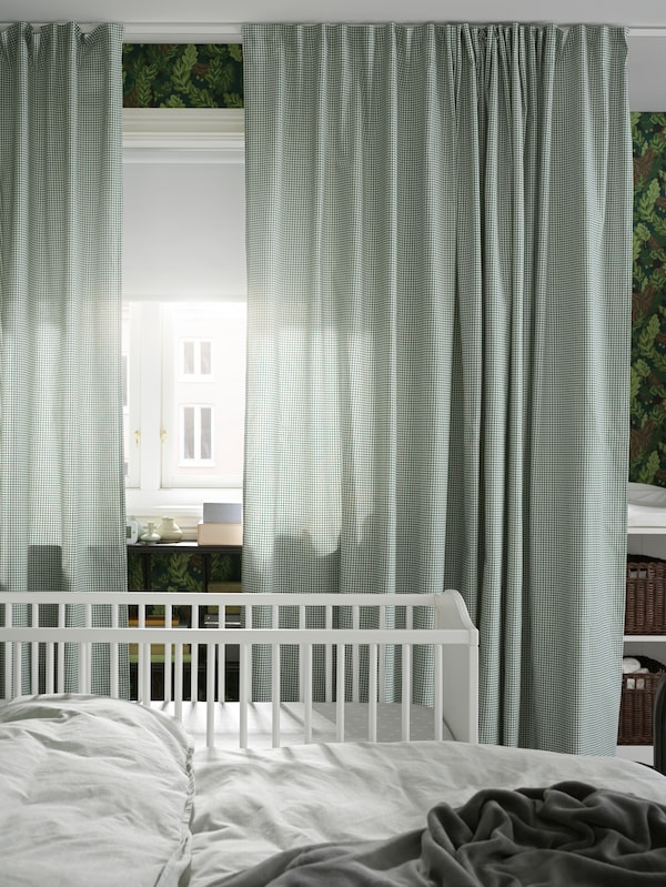 A SMÅGÖRA cot stands next to a SAGSTUA double bed near a window with ORDENSFLY curtains and a FRIDANS roller blind.