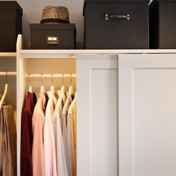 HAUGA 豪嘉 衣柜组合,推拉门打开,里面放着衣物。衣柜顶上放着黑色的储物盒和一顶帽子。