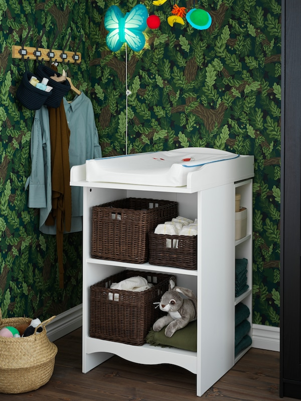 A SMÅGÖRA changing table/bookshelf with its shelves holding baskets of essentials for a baby stands in a bedroom.