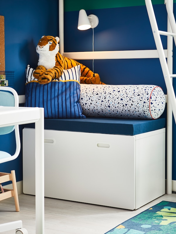 A white STUVA/FRITIDS bench with toy storage with cushions and a tiger soft toy on top sits beneath a VITVAL loft bed.