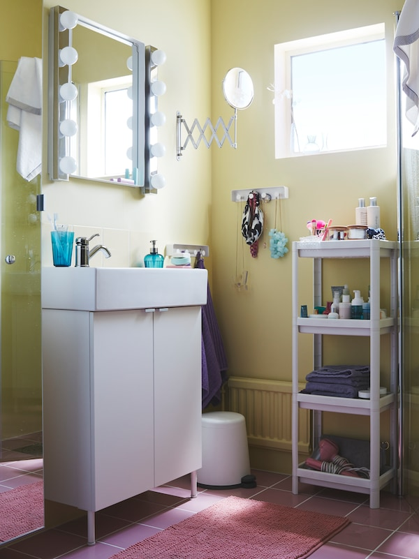 A small bathroom with a tiny window, a white wash-basin cabinet with 2 doors and a mirror with 2 LED wall lamps on the side.