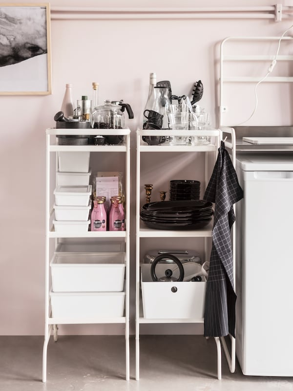 Two white trolleys stand against a pale pink wall in a kitchen and store kitchen supplies and tableware.