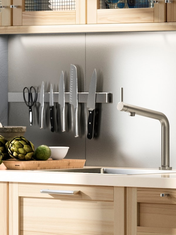 A kitchen with wooden cabinets and a white worktop, a stainless steel-coloured wall panel and a magnetic knife rack.