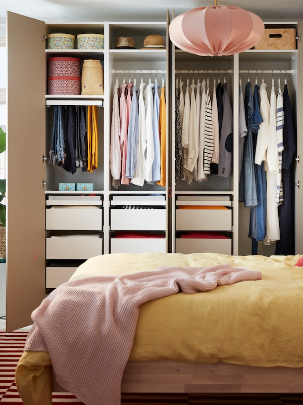 An open PAX/REINSVOLL wardrobe filled with clothes, by a bed covered with yellow PUDERVIVA bed linen and an INGABRITTA throw.