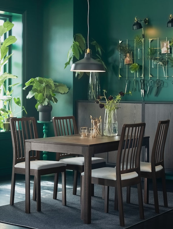 A living room with green walls and plants with an EKEDALEN dining table and four upholstered chairs in dark brown.