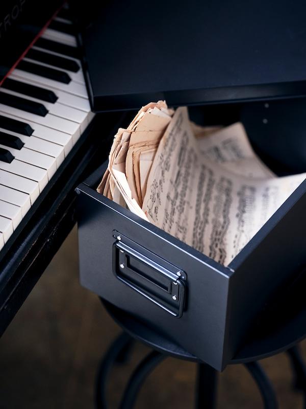 钢琴旁的凳子上放着一个黑色的MANICK 马尼克 附盖储物盒,里面装着乐谱。