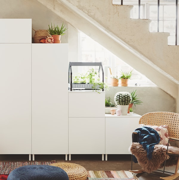 A white PLATSA storage combination, consisting of units of different heights, stands under the stairs in a home.