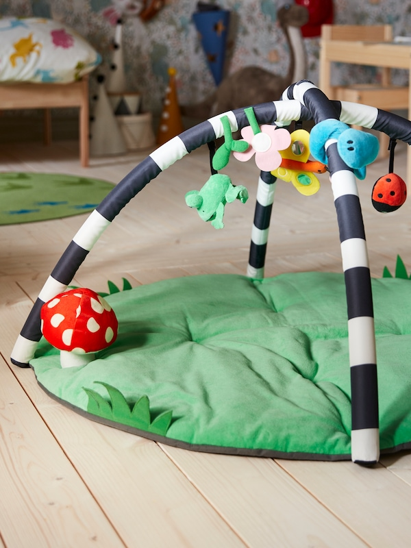 A KLAPPA baby gym on a wooden floor with a green base with a mushroom toy, and ladybug, butterfly and frog toys overhead.