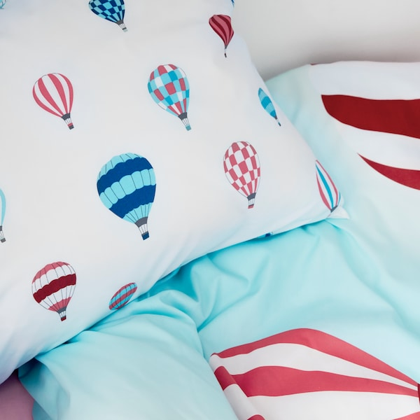 A pillow and a duvet with an UPPTÅG pillowcase and quilt cover with hot air balloon patterns lie on the head of a bed.
