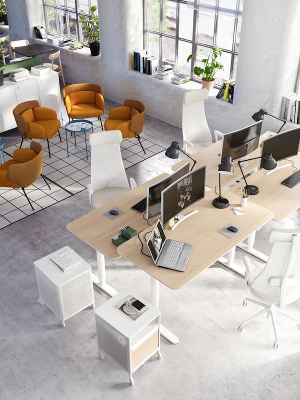 办公室中摆放着四张白色/橡木书桌,桌上放着电脑和黑色工作灯,旁边还立着两个白色抽屉柜。