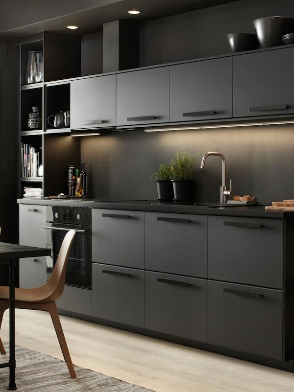 时尚的黑色厨房,顶部橱柜下方有照明。台面上放着两个黑色花盆,栽种了植物。