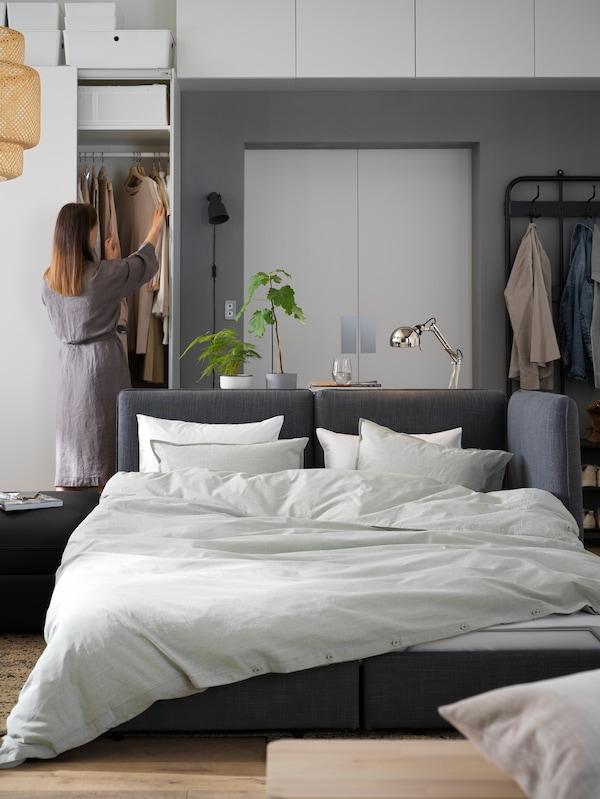 由两个VALLENTUNA 瓦伦图 沙发床模块改装成的双人床,铺上了被子和枕头,背景中有一位女士。