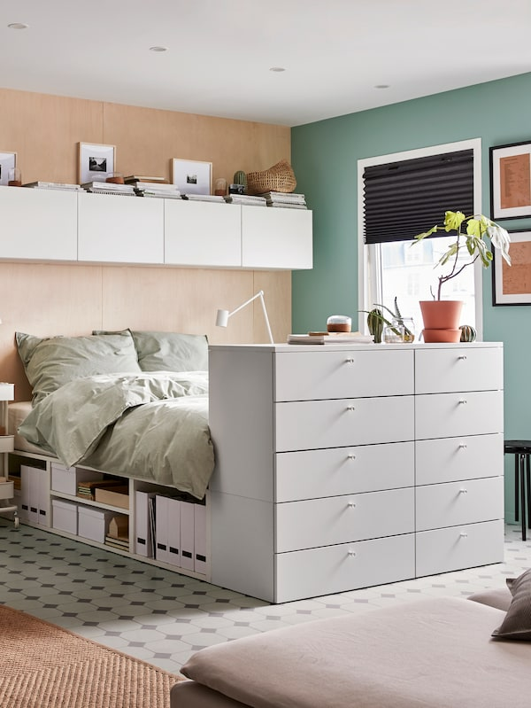 A PLATSA bed with 10 drawers and BERGPALM bed linen stands under a row of PLATSA wall storage in a corner near a window.