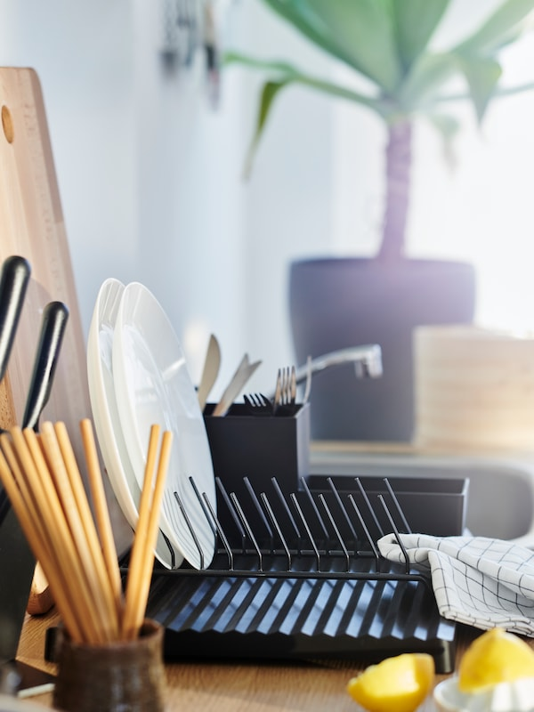 A black dish drainer with a kitchen utensil rack and a plate holder, two white plates, wooden chopsticks and a tea towel.