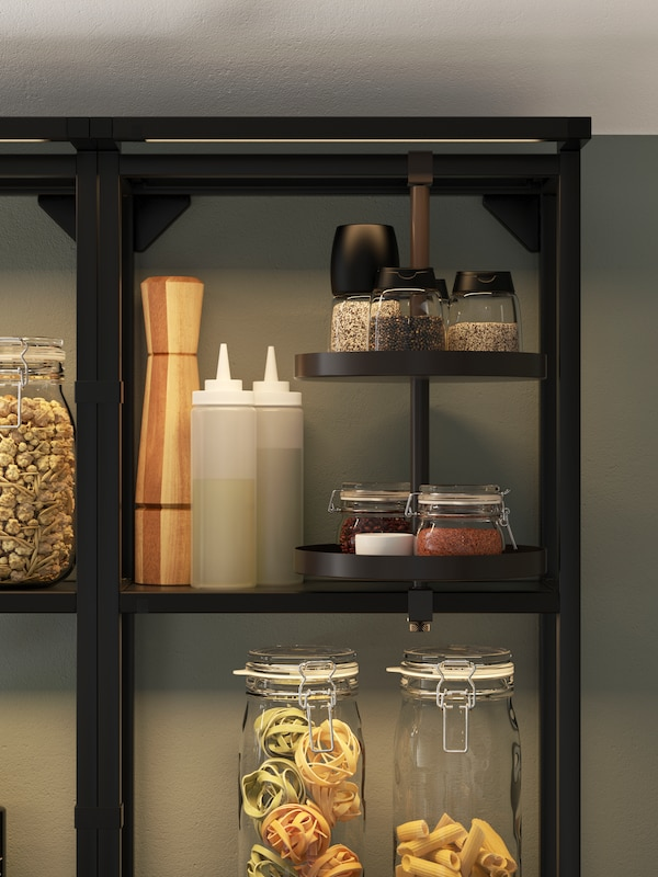 A black open shelf with integrated lighting and a swivel shelf, storing glass jars with pasta, spice mills, and condiments.