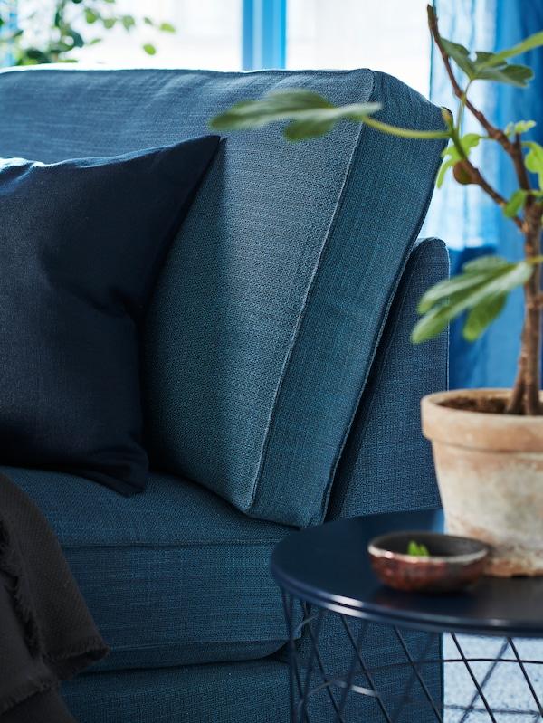 蓝色的KIVIK 奇维 贵妃椅角上摆着一张蓝色边桌,上面还放了一棵植物。