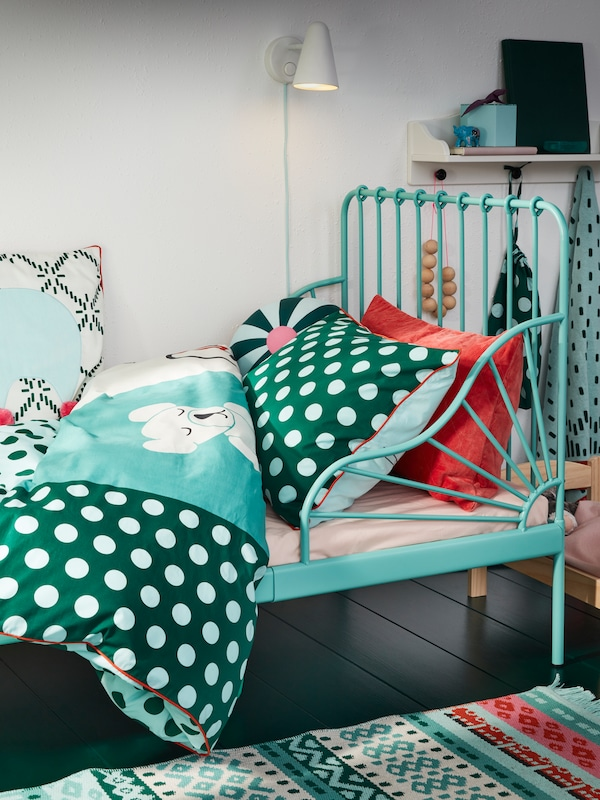 An extendable bed frame in turquoise and KÄPPHÄST printed bed linen in turquoise, green and white.