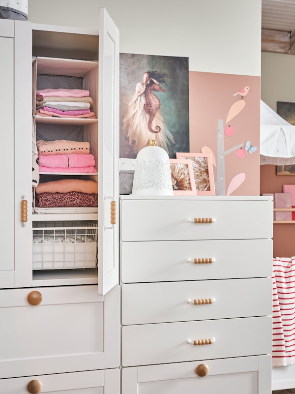 A SMÅSTAD wardrobe and chest of drawers. Inside the wardrobe is a RASSLA storage with 5 compartments holding clothes.