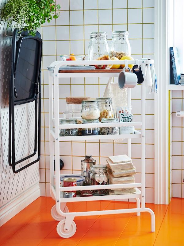 厨房一角有一辆白色SUNNERSTA 苏纳思 推车,上面放有几罐食品、一些碟子、茶杯和餐巾纸。