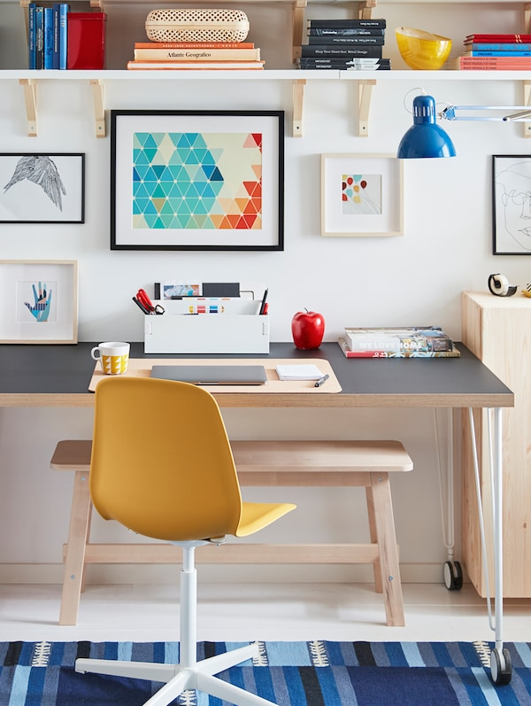 A yellow chair in front of a desk, various writing and study items on the desk, pictures on the wall, a blue lamp.