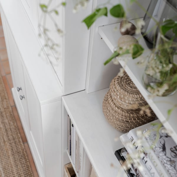 A white HAVSTA bookcase holding books, baskets and plants stands beside a white storage unit with closed doors.