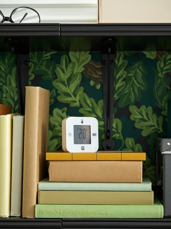 A KLOCKIS clock/thermometer/alarm/timer stands on books on a shelf on a wall covered with leaf-patterned wallpaper.