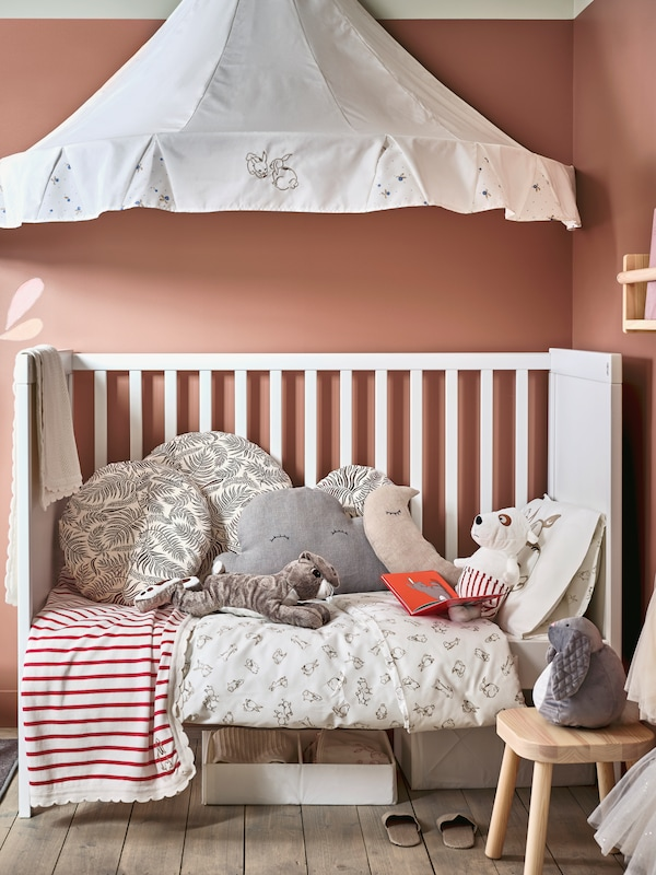 A children's room where a SUNDVIK cot with cosy cushions and soft toys sits under a white RÖDHAKE bed canopy.
