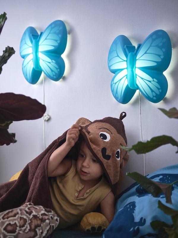 一个孩子披着猴子图案的斗篷,浅紫色墙上有两盏蝴蝶形状的壁灯。